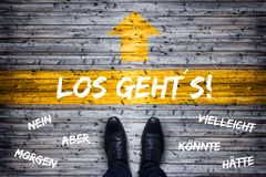 German Business Concept - Translation: Here We Go! - Black Shoes At Starting Line royalty free stock photo