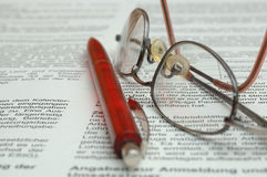 German business report. Business report in German, with glasses and red pen Stock Photo