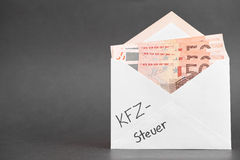 German car tax. Envelope with 50 euro bills and the german words for car tax written on it for your concepts - copy space to the left stock image