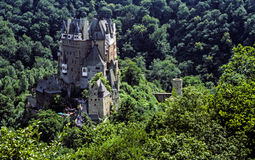 Majestic German castle surrounded by forest of trees. Beautiful grey stone German castle surrounded by forest of green trees Stock Photography