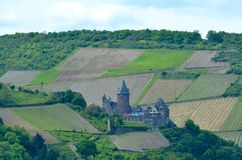 A German castle is surrounded tilled fields and forest. stock photography