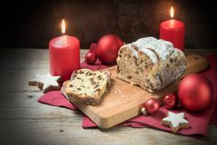 German Christmas cake, called criststollen with raisins and fruit, decoration from star cookies, red candles and balls on rustic stock image