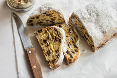 German Christmas stollen with cut off slices on parchment paper, white concrete background, knife, lit candle, minimalist style Royalty Free Stock Photo