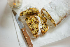 German Christmas stollen with cut off slices on parchment paper, white concrete background, knife, lit candle, top view royalty free stock photos