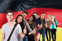 German classes. Group Of Multi Ethnic Students Standing In Front Of German Flag Showing Thumb Up Stock Image