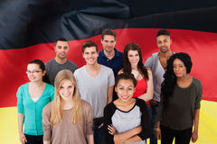 German Classes. Happy Multi-ethnic Group Of People Standing In Front Of German Flag Stock Image
