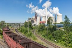 German Coal-fired power plant with empty cargo train near Garzweiler mine. Coal-fired power plant with rempty cargo train near Garzweiler open pit mine in royalty free stock image