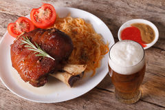 German cuisine: Baked shank and sauerkraut closeup and beer Stock Images