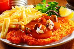 German Cuisine - Gourmet Jägerschnitzel and Fries. Close up Appetizing German Cuisine - Gourmet Jägerschnitzel with Sauce and Crispy Potato Fries on White stock photo