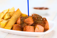German Currywurst. German fast food called Currywurst served with French fries on a disposable plate with plastic party fork (Selective Focus, Focus on the front Stock Photos