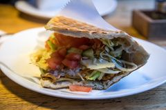 German Döner Kebab in pita flatbread with salad and chicken meat on plate stock photos