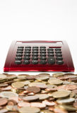 German Euro coins infront of a red calculator isolated on white Stock Photography