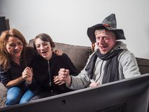 German family is watching football world cup soccer on tv. Together on sofa at home. They are having fun as their team is winning - copy space Royalty Free Stock Photo