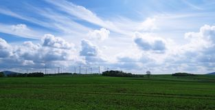 German Farm Land and Wind Turbines. Flat farm land with wind turbines under dramatic blue sky in the background, somewhere in Sauerland Germany Stock Photos
