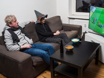 Father and son watching football world cup soccer on tv stock images