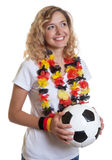 German female soccer fan with ball looking sideways Royalty Free Stock Image