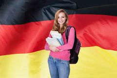 German Female Student. Young Female Student Holding Books In Front Of German Flag Royalty Free Stock Photo