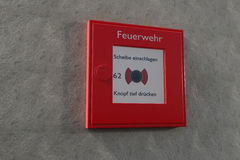German fire alarm box on a grey wall with copyspace Royalty Free Stock Photo