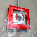 German fire detector. Fire detector in red and white at a grey wall in rising smoke Stock Photography
