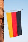 German flag. Hanging vertical against blue sky stock images