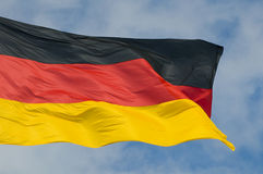 German Flag. The German flag flying against a partly cloudy sky stock photography