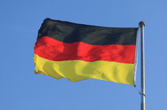 German flag. Waving German flag with blue sky stock photo