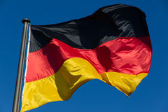 German flag. (black-red-gold) in the wind in front of a blue sky background royalty free stock image