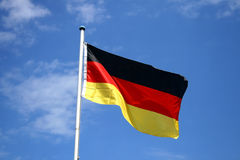German flag. A german flag in front of clouds stock photography