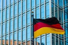 German flag on the background of office building, Atlanta, USA. German flag closeup on the background of facade of office skyscraper, Atlanta, USA Royalty Free Stock Image