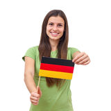 German Flag. Beautiful young woman holding German Flag over white background royalty free stock photo