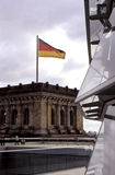 German flag- Berlin, Germany. Flag flying from Hans Scharoun's Philharmonic hall as viewed from the Reichstag building (seat of German Parliament)- Berlin Royalty Free Stock Images