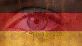 German flag with blinking eye. Digital composite of German flag with a close-up of a pretty blue eye in the background blinking stock video