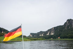 German flag at ferry through the Elbe at Kurort Rathen village and Bastei rocks Stock Images