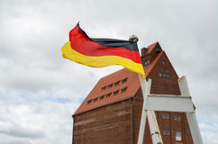 German flag flaps on the wind in historical harbor of Stralsund stock image