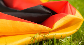 German flag on the green grass on sunny day,  closeup. German flag on the green grass,  closeup, background Royalty Free Stock Image