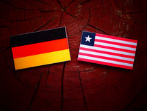 German flag with Liberian flag on a tree stump isolated. German flag with Liberian flag on a tree stump Stock Images