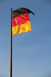 German flag on a stick. Waving in the wind against the blue sky, consisting of three equal horizontal bands: upper - black, medium - red and the bottom is Royalty Free Stock Photography