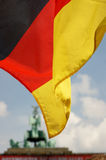 The German flag waves in the foreground with the Brandenburg gate in the background. Royalty Free Stock Photo
