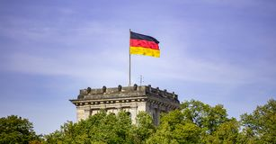 German flag waving on silver flagpole, Reichstag building in Berlin. Blue sky with clouds background royalty free stock images