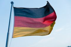 German flag in the wind. A German flag in the wind with a blue sky in the background stock images