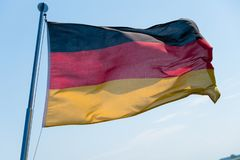 German flag in the wind. A German flag in the wind with a blue sky in the background stock image