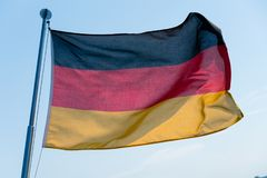 German flag in the wind. A German flag in the wind with a blue sky in the background royalty free stock photo