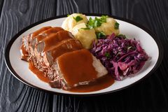 German food Sauerbraten - slowly stewed marinated beef with gravy with potato dumplings and red cabbage close-up on a plate.
