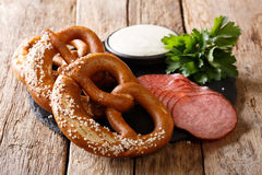 German food: sliced sausages and pretzels with cream sauce close royalty free stock photo