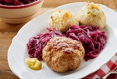 German frikadellen with dumplings. German frikadellen, a spicy meatball of minced beef or veal with dumplings and shredded red cabbage on an oval plate stock images