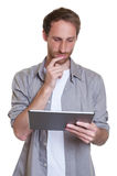 German guy reading on tablet computer Stock Photo