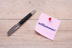 German handwritte word. `willkommen` on pink sticky note with pen stock photos