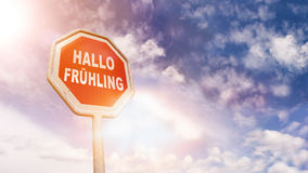 German Hello Spring wish on red traffic road stop sign. Hallo Fruehling German for Hello Spring on red traffic road stop sign in front of blue sky with clouds stock photo