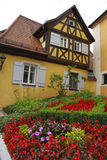German house. Outdoor image of a typical German house with colorful flowerbed in front of it stock photos
