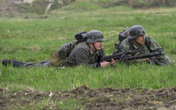 German infantryman and machine gunner with a machine gun lying in the grass. Reconstruction of the episode of the great Patriotic Stock Images